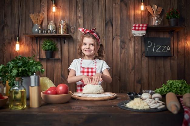 Het glimlachende meisje die witte t-shirt met geruite schort en hoofdband het kneden brooddeeg op lijst dragen vulde met ingrediënten voor pizza in modieuze houten keuken.