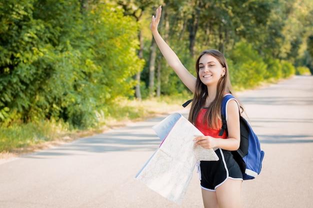 Het glimlachende meisje hief haar hand op om de auto te stoppen die op de weg rijdt om een manier te vragen
