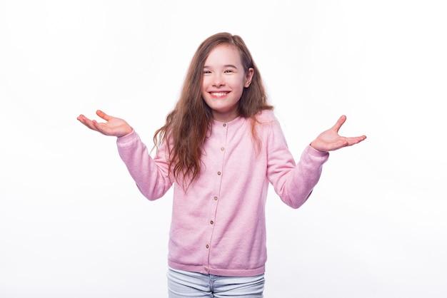 Het glimlachende meisje houdt de armen omhoog gebarend alsof ze het niet weet of wat.