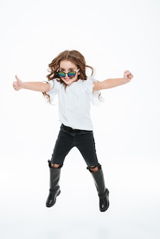 Het glimlachende meisje in en zonnebril die beduimelt omhoog springen tonen