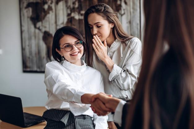 Het glimlachende meisje in glazen schudt handen met haar collega terwijl haar medewerker iets in haar oor zegt