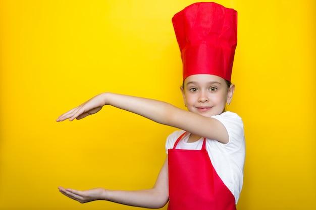 Het glimlachende meisje in het kostuum van een rode chef-kok richt met beide handen aan een exemplaarruimte op geel