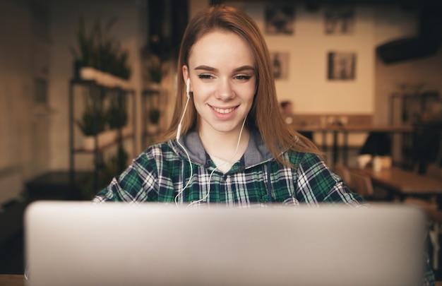 Het glimlachende meisje in vrijetijdskleding en hoofdtelefoons werkt aan laptop in een koffie, bekijkt de camera en glimlacht.