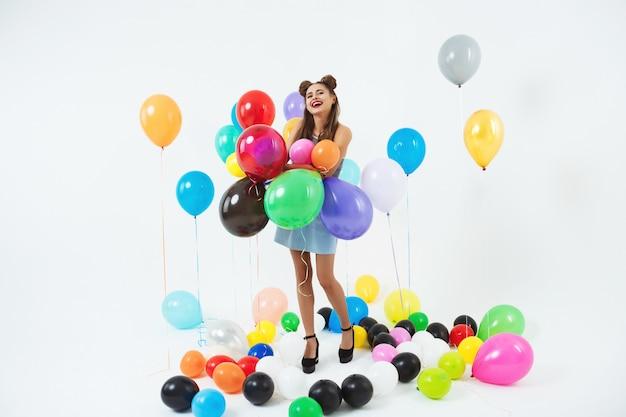 Het glimlachende meisje kijkt gelukkig holdingsbos van grote ballons