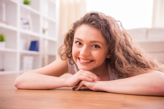 Het glimlachende meisje ligt thuis op vloer.