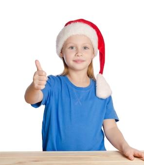 Het glimlachende meisje met duimen ondertekent omhoog in de hoed van de kerstman, die op wit wordt geïsoleerd