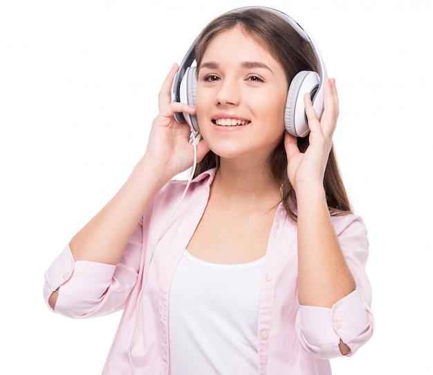 Het glimlachende meisje met hoofdtelefoon luistert een muziek.