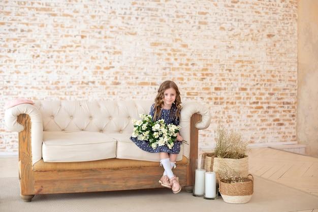 Het glimlachende meisje met krullend haar met een boeket van jasmijnbloemen zit op de bank