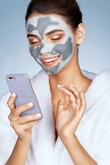 Het glimlachende meisje met masker van klei op haar gezicht en leest een bericht op de telefoon