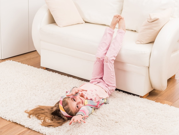 Het glimlachende meisje rekt zich in woonkamer uit