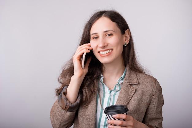 Het glimlachende meisje spreekt op de telefoon en haalt kop op wit weg
