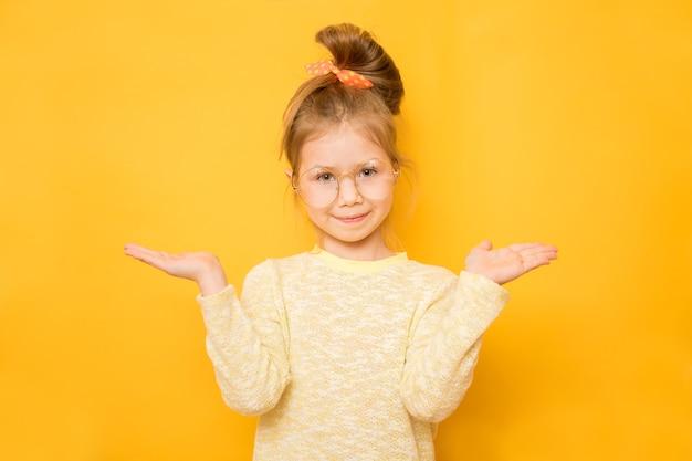 Het glimlachende meisje toont schalen op handen op gele achtergrond. kopieer ruimte op handpalmen