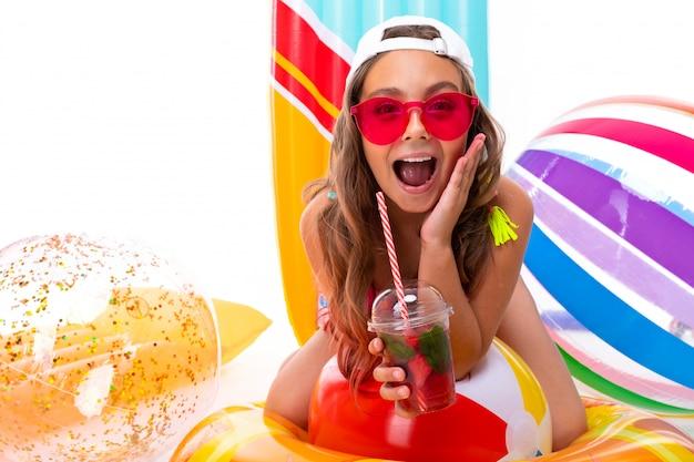 Het glimlachende meisje van de close-up op een witte achtergrond, het kind houdt niet-alcoholische cocktails in zijn handen en lacht