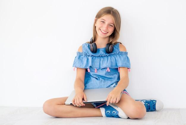 Het glimlachende meisje zit met gesloten laptop