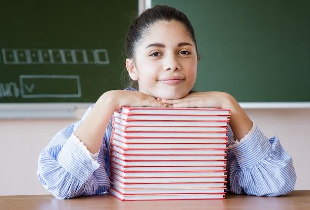Het glimlachende meisje zit tegen bord in klaslokaal