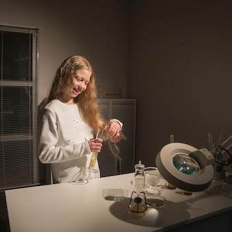 Het glimlachende meisjesschoolmeisje voert het bureau van de onderzoekchemie uit. het concept van onderwijs en hobby