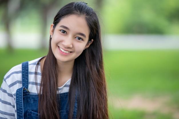 Het glimlachende mooie aziatische meisje bij boom op park in de zomer voor ontspant tijd