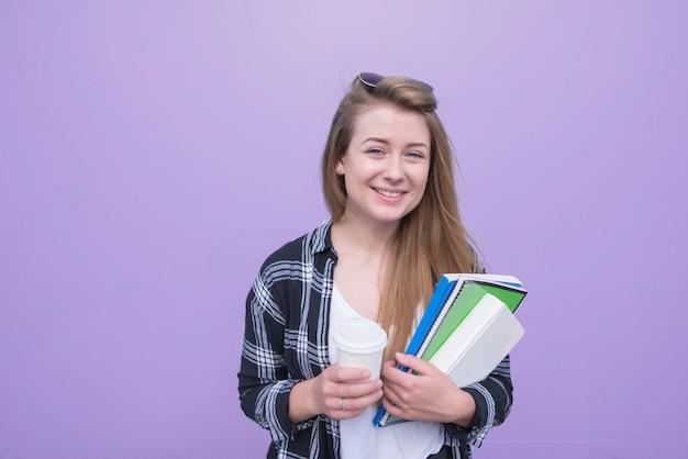 Het glimlachende mooie meisje bevindt zich op een purpere achtergrond met een kop koffie en notitieboekjes in haar handen en bekijkt de camera.