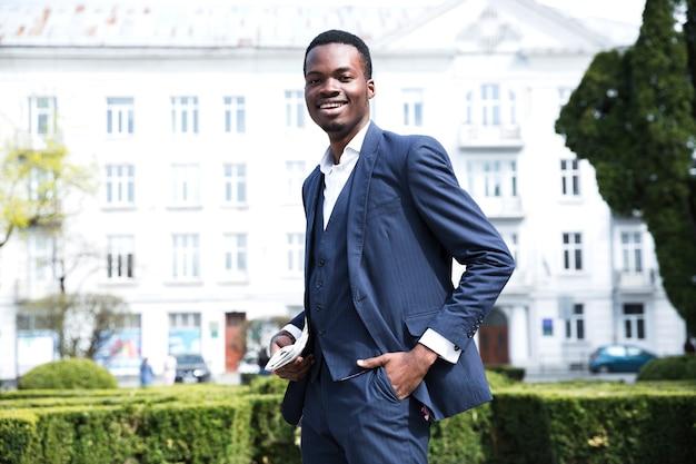 Het glimlachende portret van een jonge zakenman met dient zijn zak in bekijkend camera