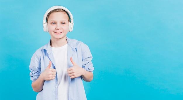 Het glimlachende portret van een jongen met witte hoofdtelefoon op zijn hoofd die duim tonen ondertekent omhoog tegen blauwe achtergrond