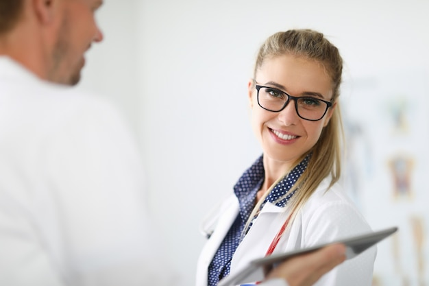 Het glimlachende portret van vrouwelijke arts met bril dichtbij collega houdt klembord uit. medische zorg en diagnose concept