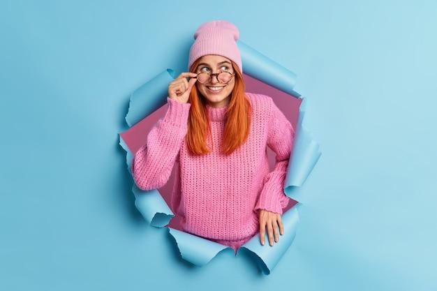 Het glimlachende roodharige schoolmeisje concentreerde zich gelukkig opzij met een doordachte gezichtsuitdrukking en houdt de hand op een bril, draagt een hoed en een roze trui.