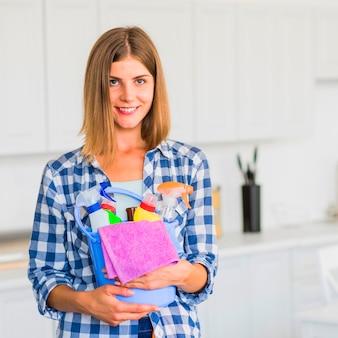 Het glimlachende schoonmakende materiaal van de huisvrouwenholding in handen