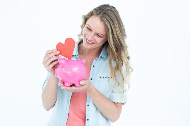 Het glimlachende spaarvarken van de vrouwenholding en rood hart