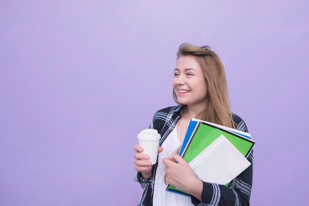 Het glimlachende studentenmeisje bevindt zich op een purpere achtergrond met notitieboekjes en een kop van koffie in zijn handen en kijkt aan de kant.
