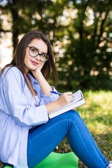 Het glimlachende studentenmeisje in jeansjasje en glazen schrijft in notitieboekje in park