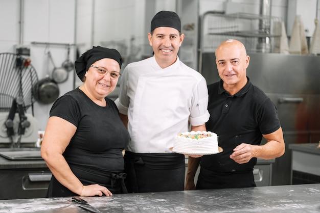 Het glimlachende team die van gebakjechef-koks een cake tonen. bakkerij werkgroep. chef-kok team.