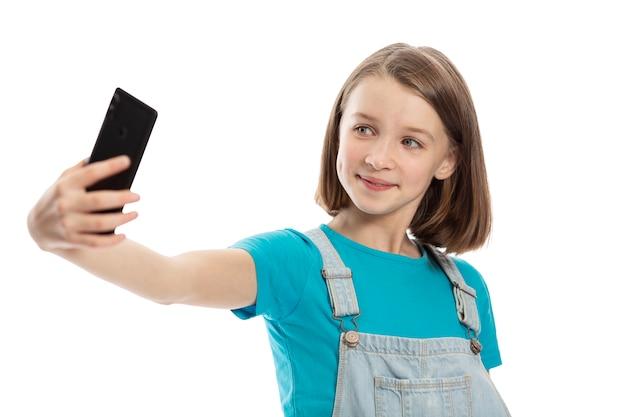 Het glimlachende tienermeisje wordt gefotografeerd op de telefoon. geã¯soleerd op een witte achtergrond.