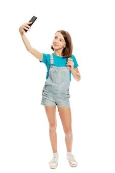 Het glimlachende tienermeisje wordt gefotografeerd op de telefoon. volledige hoogte. geã¯soleerd op een witte achtergrond.