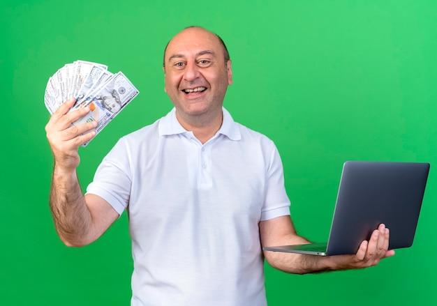 Het glimlachende toevallige geld van de volwassen manholding met laptop die op groene muur wordt geïsoleerd