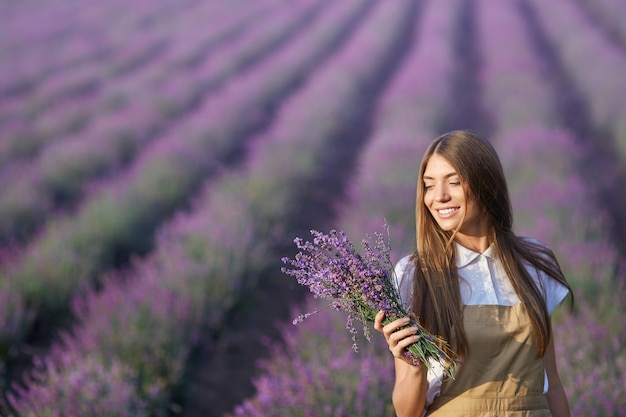Het glimlachende vrouw stellen met boeket op lavendelgebied