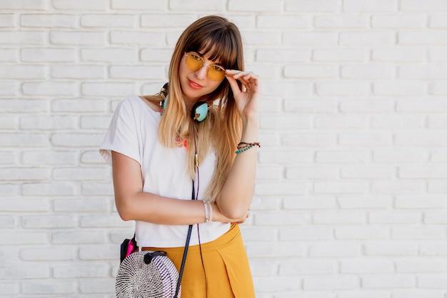 Het glimlachende vrouw stellen over witte bakstenen muur met oortelefoons