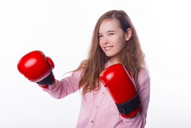 Het glimlachende vrouwelijke kind dat doos rode handschoenen draagt, is klaar om te vechten.