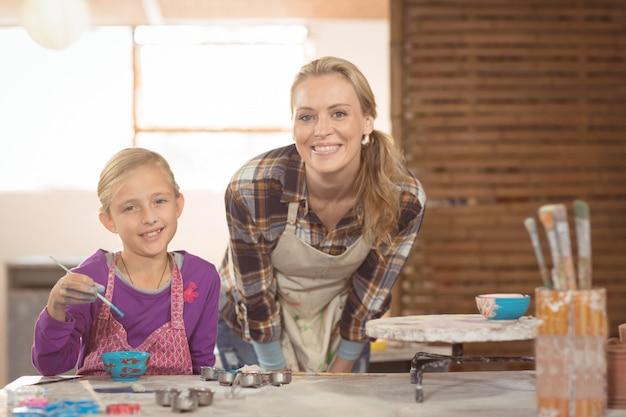 Het glimlachende vrouwelijke pottenbakker en meisjes schilderen in aardewerkworkshop