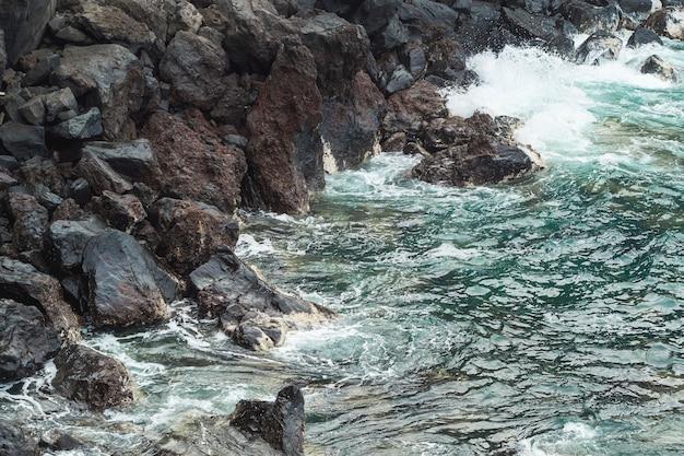 Het golvende water van de close-up bij rotsachtige kust