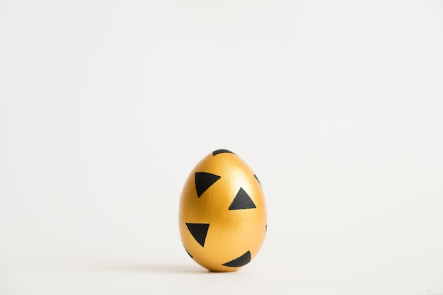 Het gouden ei van pasen met geometrisch zwart patroon dat op witte achtergrond wordt geïsoleerd
