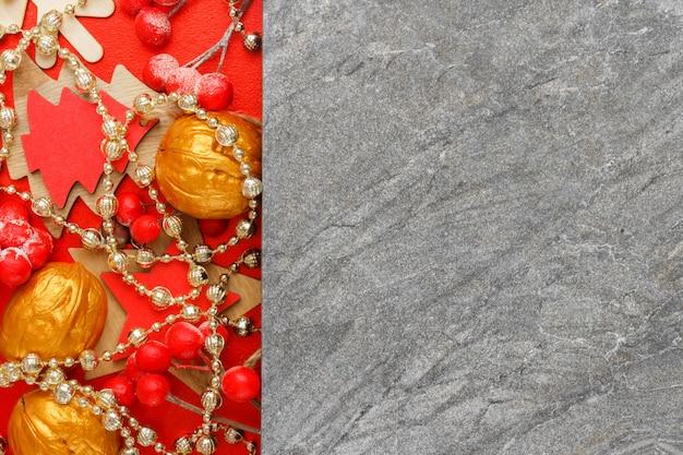 Het gouden en rode speelgoed van de nieuwjaarboom op grijze steenachtergrond met copyspace