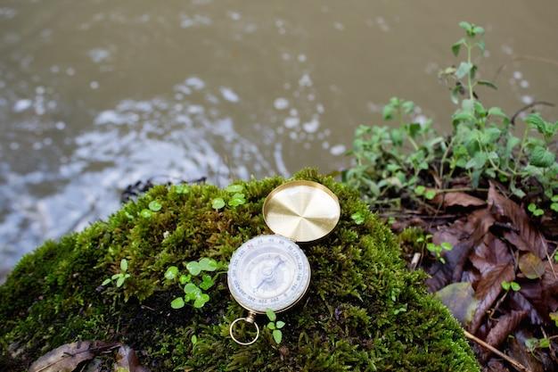 Het gouden kompas ligt op het mos bij de rivier