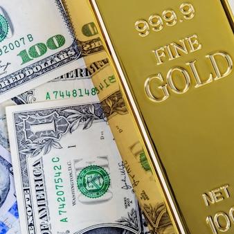 Het gouden passement van de metaalbaar op de achtergrond van dollar en euro rekeningen.