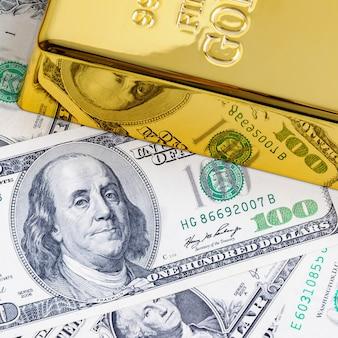 Het gouden passement van de metaalstaaf op de achtergrond van dollarrekeningen.