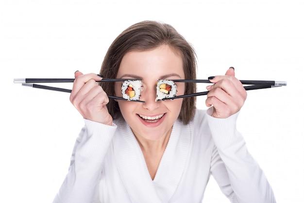 Het grappige beeld van vrouw houdt sushibroodjes op haar oog.