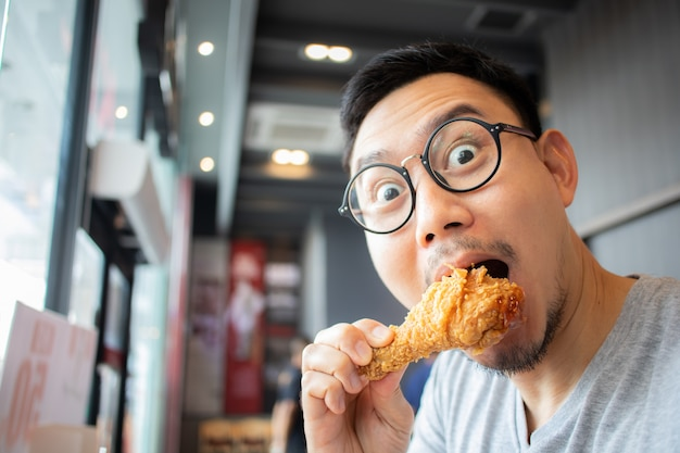 Het grappige gezicht van de mens eet gebraden kip in het concessiekoffie.