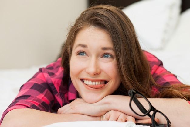 Het grappige jonge meisje ontspannen op het bed