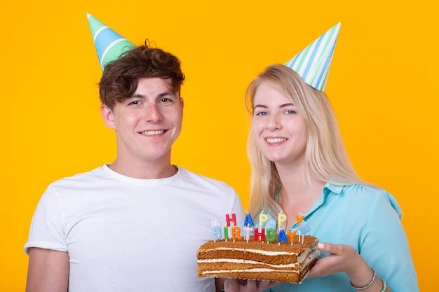Het grappige jonge stel in papieren doppen en met een cake trekt een dwaas gezicht en wenst een gelukkige verjaardag terwijl ze tegen een gele muur staan. concept van felicitaties en gek rond.