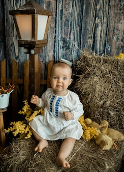 Het grappige kaukasische babymeisje in een witte linnenkleding zit op een hooiberg met eendjes. pasen vieren met kinderen