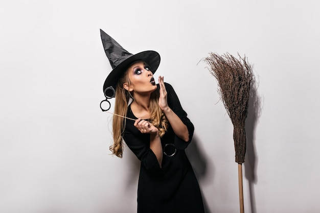 Het grappige kaukasische meisje stellen in heks kostuum in carnaval. langharige vrouw in magische hoed die zich op witte muur met bezem bevindt.